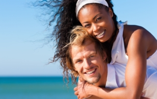 10020845 - happy couple - black woman and caucasian man - at the beach in their vacation