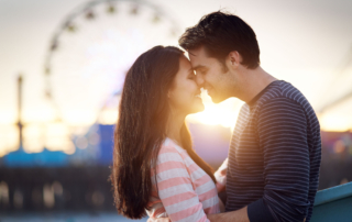 23289160 - romantic couple in front of santa monica amusement park at sunset